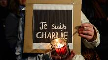 """A woman holds a candle and a poster reading """"Je suis Charlie"""" (I am Charlie) during a spontaneous vigil in front of the French embassy on January 7, 2015 in Berlin to express solidarity with employees of the French satirical weekly Charlie Hebdo that has been target of an attack by unknown gunmen. (JOHN MACDOUGALL/AFP/Getty Images)"""