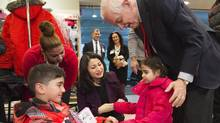 John McCallum greets Syrian refugees at Pearson International Airport in Toronto on Feb. 29. (Nathan Denette/THE CANADIAN PRESS)