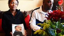 In this photo taken July 20, 2014, Chantel and Elwin Morris pose with a photo of their son, Taegrin, at their home in Boksburg, east of Johannesburg. South African media say the boy was with his sister and parents during a carjacking Saturday night. His mother told The Star newspaper that her son's foot got stuck as she tried to pull him from the car, but the carjackers sped off. The boy was later found dead in the abandoned vehicle. (Timothy Bernard/AP)