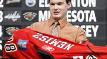 The Carolina Hurricanes acquired Calgary Flames forward Greg Nemisz as part of a two-player deal on Monday. Calgary picked up right winger Kevin Westgarth as part of the deal. In this file photo, Nemisz puts on a Calgary Flames jersey after being chosen as their first round draft pick at the NHL draft, in Ottawa Friday June 20, 2008. (FRED CHARTRAND/THE CANADIAN PRESS)