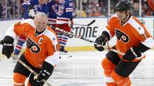 Philadelphia Flyers Bob Clarke (L) skates next to Eric Lindros before the start of the Flyers alumni versus the New York Rangers alumni during the first period of the 2012 NHL Winter Classic Alumni ice hockey game in Philadelphia, Pennsylvania December 31, 2011. REUTERS/Tim Shaffer (Tim Shaffer/Reuters)