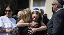 Mourners hug at a funeral service for the late Jack Rabinovich in Toronto on Wednesday, August 9, 2017. Scotiabank Giller Prize creator Rabinovitch was celebrated by friends and family members at his funeral on Wednesday, where the beloved businessman was remembered for his warmth, wit and passion for knowledge and the written word. (Christopher Katsarov/THE CANADIAN PRESS)
