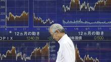 A man walks by an electronic stock board of a securities firm in Tokyo Friday, Oct. 10, 2014. Asian stocks sank Friday after Wall Street suffered its worst day of the year and weak German trade data fueled worry Europe is sliding into recession. Japan's benchmark Nikkei 225 index dropped 1.15 percent or 178.38 points and closed at 15,300.55. (Koji Sasahara/AP)