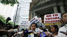 Sringatin, a member of a domestic workers union, cries outside the Court of Final Appeal in Hong Kong on March 25, 2013. Hong Kong's top court ruled against two Filipino domestic helpers seeking permanent residency Monday, the final decision in a case that affects tens of thousands of other foreign maids in the Chinese Special Administrative Region. (Kin Cheung/AP)