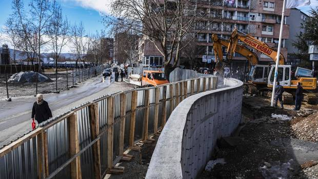 Men stand by bulldozers taking down a concrete wall near the main bridge in the town of Mitrovica on Feb. 5.