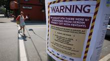 A woman walks past a sign posted by the Insite supervised injection site warning of heroin cut with fentanyl in Vancouver. (Darryl Dyck for The Globe and Mail)