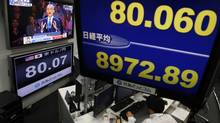 A television set shows U.S. President Barack Obama's election night victory rally, near other monitors displaying Japan's Nikkei stock average (right, bottom) and the Japanese yen's exchange rate against the U.S. dollar, at a foreign currency brokerage firm in Tokyo Nov. 7, 2012. (Toru Hanai/REUTERS)