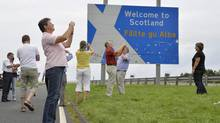 Tourists take photographs next to a road that marks the England - Scotland border, at a lay-by on the A1 road near Berwick, August 20, 2013. (TOBY MELVILLE/REUTERS)