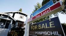 A real estate for sale sign is pictured in front of a home in Vancouver. (© Ben Nelms / Reuters)