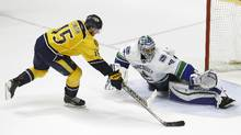 Nashville Predators centre Craig Smith (15) scores against Vancouver Canucks goalie Ryan Miller during the shootout in an NHL hockey game Thursday, March 24, 2016, in Nashville, Tenn. The Predators won 3-2. (Mark Humphrey/AP)