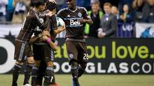 Vancouver Whitecaps' Camilo Sanvezzo, bottom, of Brazil, celebrates his goal by embracing teammate Young-Pyo Lee, second left, of South Korea, and giving him the ball as Russell Teibert, left, and Gershon Koffie, of Ghana, join them during first half MLS soccer action against the Colorado Rapids in Vancouver, B.C., on Sunday October 27, 2013. Lee announced he would be retiring from professional soccer at the conclusion of the MLS season. (DARRYL DYCK/THE CANADIAN PRESS)