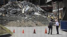 Two men stand outside the collapsed Algo Centre Mall in Elliot Lake, Ont., on June 28, 2012. (Fred Lum/The Globe and Mail)