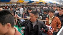 Chinese labourers queue up in a scene from Last Train Home.