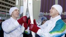 Craig Kielburger, left, hands the Olympic Flame off to his brother Marc as the Olympic Torch Relay makes its way down Yonge Street in Toronto, in December 2009. (Darren Calabrese/ The Canadian Press) (Darren Calabrese)