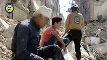 In this picture taken, Tuesday, Oct. 11, 2016, provided by the Syrian Civil Defense group known as the White Helmets, residents sit amongst rubble in rebel-held eastern Aleppo, Syria. (Uncredited/AP)