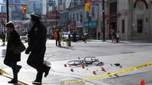 A police officer escorts a woman from the scene of a garbage truck-bicycle collision that left a woman, 38, fighting for her life in downtown Toronto on Tuesday Nov. 13, 2012. (Colin Perkel/THE CANADIAN PRESS)