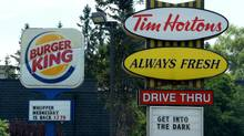 A Burger King sign and a Tim Hortons sign are displayed on St. Laurent Boulevard in Ottawa on Monday, August 25, 2014. THE CANADIAN PRESS/Sean Kilpatrick (Sean Kilpatrick/THE CANADIAN PRESS)