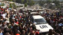 A UN vehicle is surrounded by residents of the Petinville neighbourhood of Port-au-Prince where massive tent villages have risen during a distribution of food by the United Nations World Food Program. (Win McNamee/2010 Getty Images)