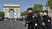French Police officers patrol the Champs Elysees near the Arc de Triomphe monument in Paris on April 21, 2017 (Philippe Lopez/AFP)