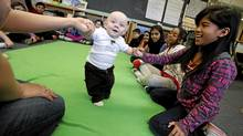 Nine-year-old Joyce Garsain helps eight-month-old Patrick Duffy as a grade four class looks on at George Webster Elementary school in Toronto. Roots of Empathy is an evidence-based classroom program that has shown dramatic effect in reducing levels of aggression among schoolchildren. (Deborah Baic/Deborah Baic /The Globe and Mail)