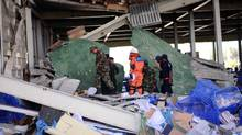 Officials stand guard amid efforts to clear rubble after a portion of the roof of a shoe factory collapsed Thursday in Cambodia, killing two people.