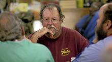 """Kevin Parham, 47, centre, talks with friends while eating dinner at Rowan Helping Ministries, a homeless shelter in Salisbury, N.C., on Mon., Oct. 31, 2011. """" (JOHN W. ADKISSON/John W. Adkisson for The Globe and Mail)"""