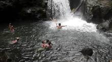 Costa Rican families enjoy a river heated by volcanic vents in a protected rainforest near San Carlos, Costa Rica, April 11, 2006. (KENT GILBERT/AP)