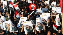 Supporters of Iraqi Shiite cleric Moqtada al-Sadr hold posters of prominent Shiite cleric Nimr al-Nimr during a demonstration in Baghdad Monday. (AHMAD AL-RUBAYE/AFP/Getty Images)
