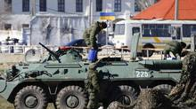 Armed men, believed to be Russian servicemen, supply an armoured personnel carrier in front of a Ukrainian marine base in the Crimean port city of Feodosia on March 23, 2014. (SHAMIL ZHUMATOV/REUTERS)