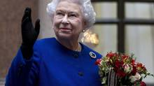 Britain's Queen Elizabeth II looks up and waves to members of staff of The Foreign and Commonwealth Office on Dec. 18, 2012 as she ends an official visit. Queen Elizabeth has been taken to the King Edward VII hospital in central London suffering from gastroenteritis, Sunday, March 3, 2013. (Alastair Grant/AP)