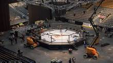 Crews work to finish assembling the UFC octagon in Toronto on Friday, December 9, 2011. (Pawel Dwulit/THE CANADIAN PRESS)