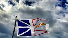 The Newfoundland flag blows in the wind in Ferryland, NL, August 8, 2013. (Jonathan Hayward/The Canadian Press)