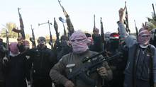 Masked Sunni gunmen chant slogans during a protest against Iraq's Shiite-led government, demanding that the Iraqi army not try to enter the city, in Falluja, 50 km (31 miles) west of Baghdad January 7, 2014. (STRINGER/IRAQ/REUTERS)