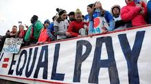 FILE - In this April 6, 2016, file photo, fans stand behind a large sign for equal pay for the women's soccer team during an international friendly soccer match between the United States and Colombia at Pratt & Whitney Stadium at Rentschler Field in East Hartford, Conn. At the current rate, women in the U.S. aren't expected to reach overall pay parity until 2059, according to the Institute for Women's Policy Research.
