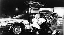 """Inventor Doc Brown (Christopher Lloyd) explains the workings of his DeLorean time machine to a fascinated Marty McFly (Michael J. Fox) in """"Back to the Future."""". (File photo, 1985) (Universal City Studios)"""