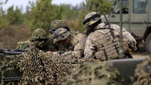 Master Corporal Maxime Daneau,left, of the 1st Battalion, Royal 22e Régiment, confirms plans to delay an enemy advance with a Polish and two Latvian soldiers during a multinational anti-tank exercise, in Pabrade, Lithuania on May 14, 2016. (Captain Mark Ruban/Operation Reassurance Land Task Force)