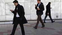 Workers look at their phones while walking at the Canary Wharf business district in London February 26, 2014. (EDDIE KEOGH/REUTERS)