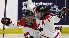 Canada forward Caroline Ouellette, right, and defenseman Tessa Bonhomme celebrate the winning goal in overtime over the United States in the gold medal game of the World Women's Ice Hockey Championships, Saturday, April 14, 2012, in Burlington, Vt. (Toby Talbot/AP)