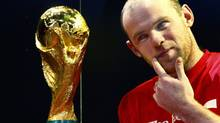 England and Manchester United footballer Wayne Rooney checks out the FIFA World Cup Trophy. (Kirsty Wigglesworth/AP)