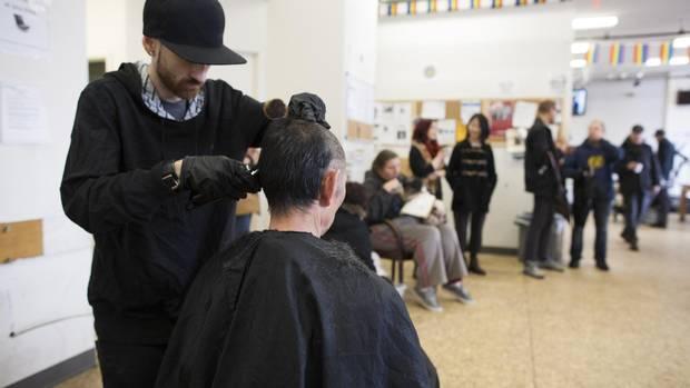 Josh Malcolm da Rua, Bandido Barbeiros corta um cabelo de clientes como de outros que esperar na fila pela sua vez na Sala de estar Drop-in abrigo em dezembro. - Esses Barbeiros Estão Dando Baixa Renda Vancouverites Mais Do Que Apenas Cortes De Cabelo