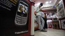 An Indian man checks his handset at a shop in Hyderabad, India, Friday, Aug. 13, 2010. (Mahesh Kumar A/AP)