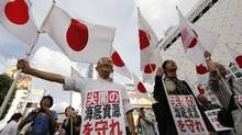 "Protesters hold up Japanese flags at an anti-China rally in Tokyo, Sept. 18, 2012. The signs read, ""Protect Senkaku's submarine resources."" (Kim Kyung-Hoon/Reuters)"