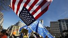 An Occupy DC demonstrator waves a flag in McPherson Square in Washington, Jan. 30, 2012. (KEVIN LAMARQUE/REUTERS)
