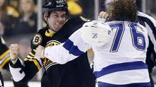 Fights, such as this one between the Boston Bruins' Adam McQuaid and Pierre-Cedric Labrie of the Tampa Bay Lightning, are the cartoon of professional hockey, but it is increasingly seen as not funny at all. Particularly when players are injured. (Michael Dwyer/the Associated Press)