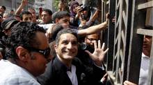 Egyptian popular television satirist Bassem Youssef, who has come to be known as Egypt's Jon Stewart, waves to is supporters as he enters Egypt's state prosecutors office to face accusations of insulting Islam and the country's Islamist leader in Cairo on March 31, 2013. (Amr Nabil/Associated Press)