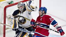 Buffalo Sabres goalie Jhonas Enroth defelcts a flying puck with his glove in front of Montreal Canadiens' Brian Gionta during third period NHL action in Montreal Tuesday, March 19, 2013. The Sabres went on to beat the Canadiens 3-2 in overtime. (Paul Chiasson/THE CANADIAN PRESS)