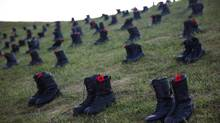Military boots and poppies lay around the Canadian National Vimy Memorial ahead of a Sunset Ceremony on April 8, 2017 in Vimy, France. (Jack Taylor/Getty Images)