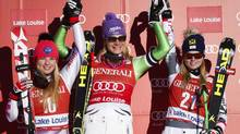 Germany's Maria Hoefl-Riesch, centre, celebrates her victory with second place finisher Liechtenstein's Tina Weirather, left, and third place finisher Austria's Anna Fenninger following the women's World Cup downhill ski race in Lake Louise, Alta., Saturday, Dec. 7, 2013. (Jeff McIntosh/THE CANADIAN PRESS)