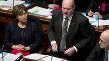 Premier Christy Clark, left, looks on as B.C. Finance Minister Mike de Jong tables the budget in the B.C. Legislature in Victoria on Feb. 19, 2013. (Jonathan Hayward/The Canadian Press)