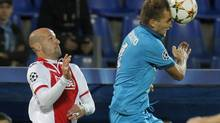 Zenit's Domenico Criscito, right, fights for the ball with Standard de Liege's Laurent Ciman during the UEFA Champions League, play offs, 2nd leg soccer match, between Standard de Liege and Zenit St. Petersburg in St.Petersburg, Russia, Tuesday, Aug. 26, 2014. (Dmitry Lovetsky/AP)